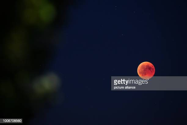 The Earth's shadow obscures the full moon During the longest lunar eclipse of the 21st century the moon dives into the Earth's shadow Photo Daniel...