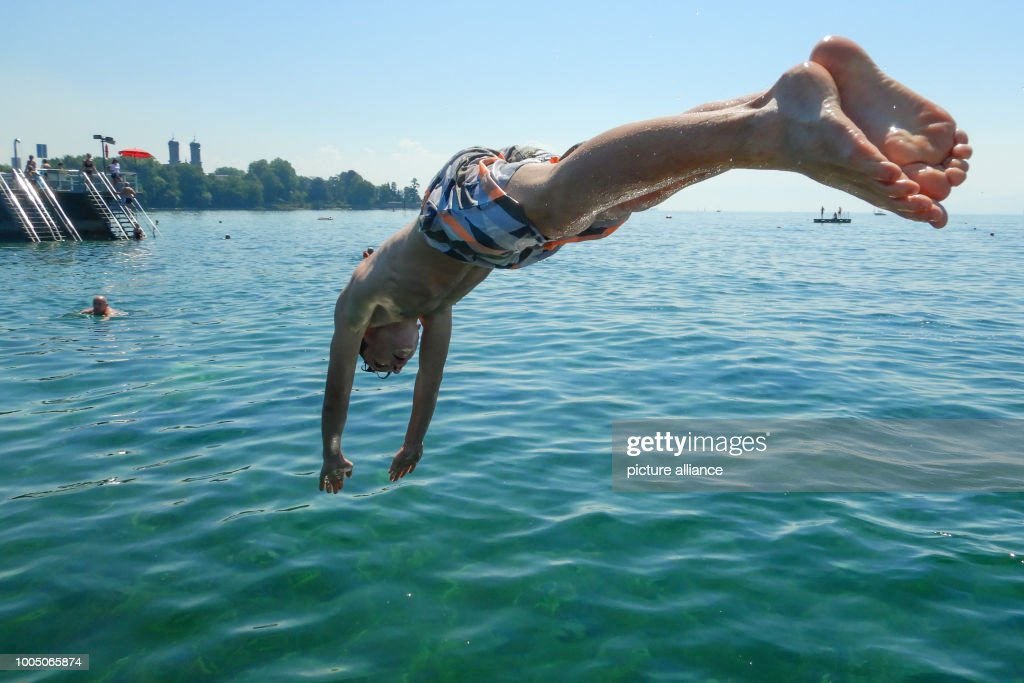 A swimmer jumps from the raft into Lake Constance in the lido. Lake Constance has a water temperature of around 24 degrees Celsius. Photo: Felix Kästle/dpa