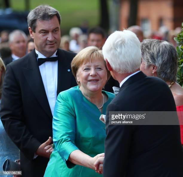German Chancellor Angela Merkel and Bavarian Minister President Markus Soeder greet Bayreuth's mayor Brigitte MerkErbe and her husband Thomas outside...