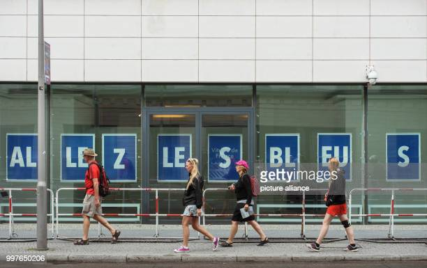 Pedestrians walking past big white letters 'Allez les Bleus' on a blue background on the windows of the French emnbassy in Berlin 'Alles les Bleus'...