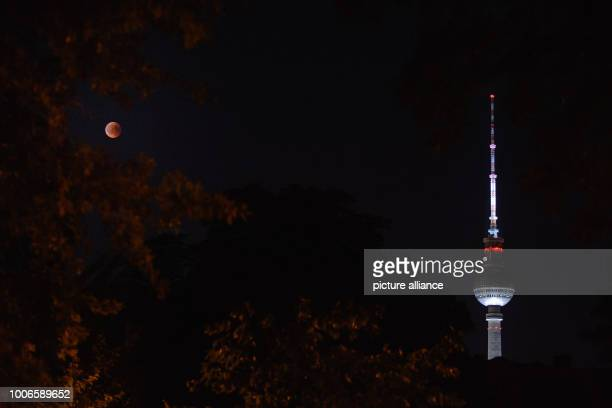 The Earth's shadow obscures the full moon next to the TV tower During the longest lunar eclipse of the 21st century the moon dives into the Earth's...
