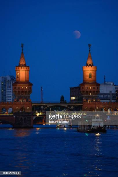 The full moon appears over the Oberbaumbrücke bridge over the Spree During the longest lunar eclipse of the 21st century the moon dives into the...
