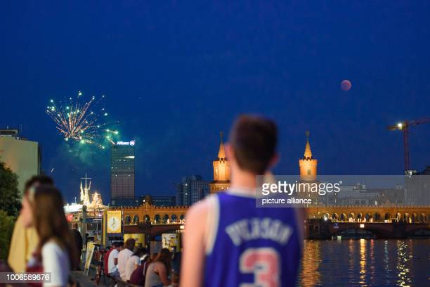 The full moon appears over the Oberbaumbrücke bridge over the Spree while Berliners watch fireworks on the banks of the Spree During the longest...