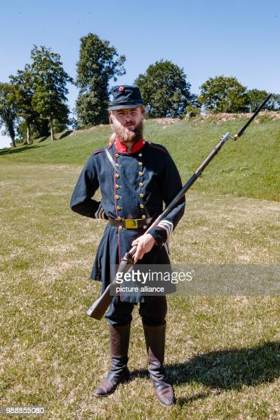 An employee of the Danevirke Museum is dressed in a historic Danish military uniform standing at the medieval Danish fortification site Danevirke...