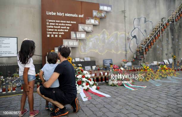 Participants of the mourning ceremony for the victims of the Loveparade accident stand in front of the memorial On 24 July 2010 21 people were...