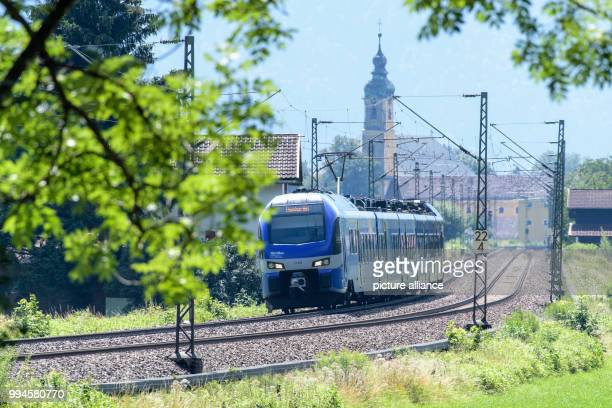 A train of the Austrian Federal Railways driving over the tracks of the Bahntrasse through the valley of the Inn between Rosenheim and Kufstein The...