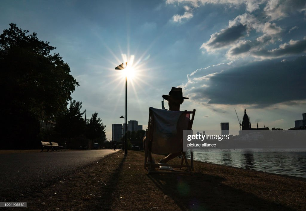 A Man On A Deck Chair Enjoying The Low Hanging Sunu0027s Light At Evening At
