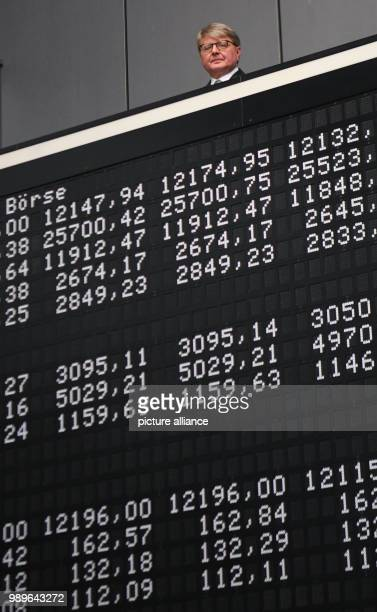 Chairman of the Deutsche Boerse AG Theodor Weimer Frank Mella standing over a display board with the indexes of the German stock exchange for the 30...