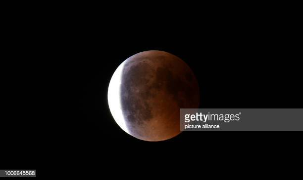 July 2018, Germany, Klausen: The reddish shimmering full moon stands above the pilgrimage church. During the longest lunar eclipse of the 21st...