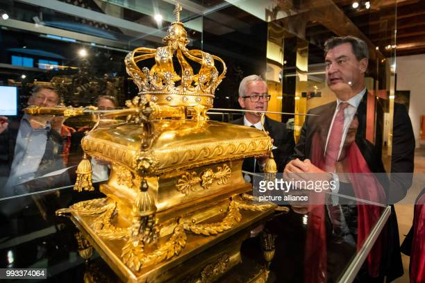 Bavarian Minister President Markus Soeder of the Christian Social Union inspects golden crowning treasures dating back to 1813 on display at the...