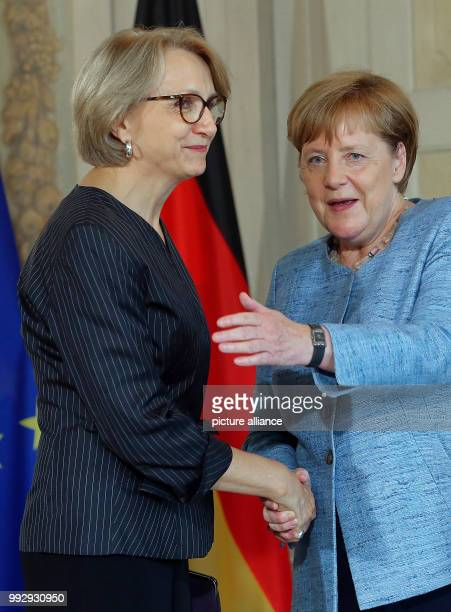 German chancellor Angela Merkel shakes hands with AnneMarie Descotes embassador of the USA during the reception for the Diplomatic corps an annual...