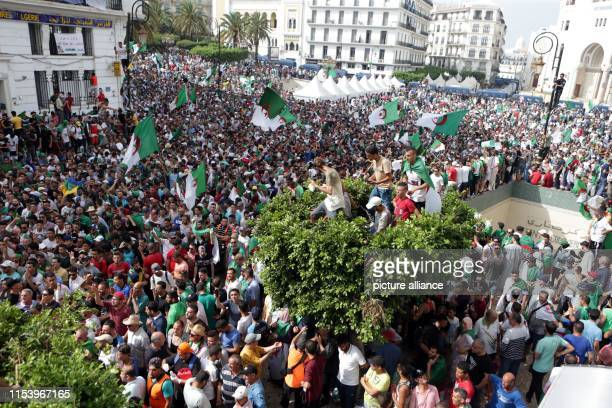 Algerians hold national flags and placrds as they take part in a march calling for the departure of the Algerian regime coinciding with the Algerian...
