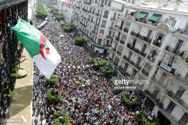 July 2019, Algeria, Algiers: Algerians hold national flags and placrds as they take part in a march calling for the departure of the Algerian regime...