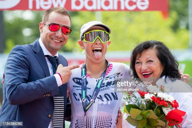 Sarah Crowley triathlete from Australia jubilantly finishes second at the Datev Challenge Roth next to the managing directors of TEAMCHALLENGE GmbH...