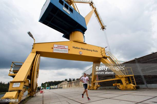 Jesper Svensson triathlete from Sweden runs along the harbour during the running stage of the Datev Challenge Roth In the 18th edition of the...
