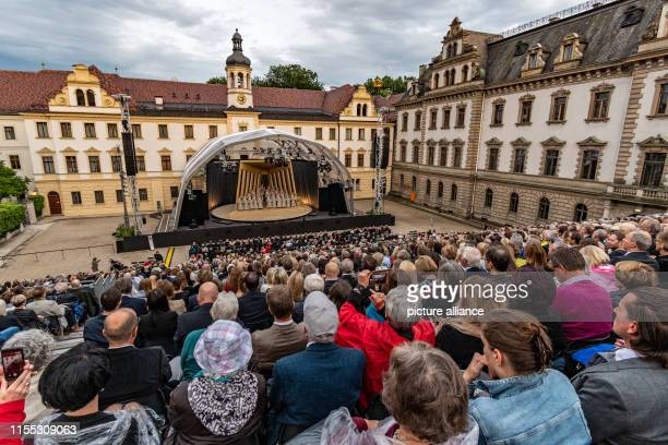Spectators sit during the ThurnundTaxis Castle Festival with the opera Nabucco in the inner courtyard of the Princely Castle of St Emmeram With a...