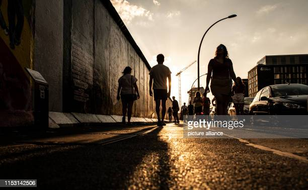 In the evening passersby go for a walk at the East Side Gallery Photo Paul Zinken/dpa