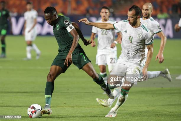 July 2019, Egypt, Cairo: Algeria's Djamel Benlamri and Nigeria's Ahmed Musa battle for the ball during the 2019 Africa Cup of Nations semi-final...
