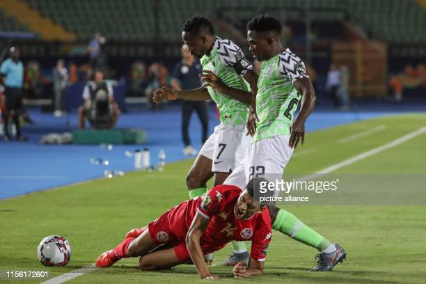 July 2019, Egypt, Cairo: Nigeria's Ahmed Musa and Nigeria's Kenneth Omeruo battle for the ball with Tunisia's Mohamed Drager during the 2019 Africa...