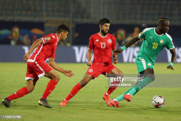 Senegal's Mbaye Diagne battles for the ball with Tunisia's Ferjani Sassi and Naim Sliti during the 2019 Africa Cup of Nations semifinal soccer match...