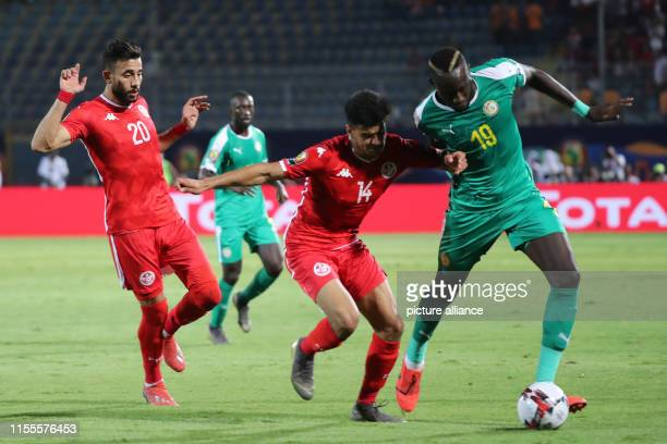 Senegal's Mbaye Diagne battles for the ball with Tunisia's Mohamed Drager and Ghaylene Chaalali during the 2019 Africa Cup of Nations semifinal...