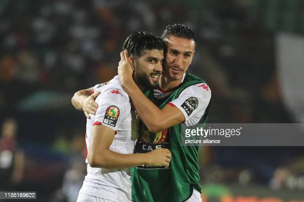July 2019, Egypt, Cairo: Tunisia's Ferjani Sassi celebrates scoring his side's first goal with team mate Karim Aouadhi during the 2019 Africa Cup of...