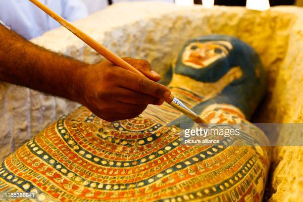 An Egyptian archaeological expert works on a newly discovered Pharaonic sarcophagi which according to Egyptian authorities dates bake to the Middle...