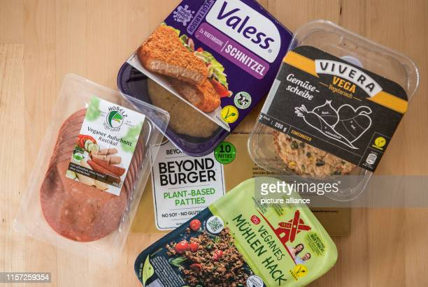 July 2019, Hessen, Frankfurt/Main: Various vegan and vegetarian meat substitutes are packaged on the table. More and more meat replacement products...