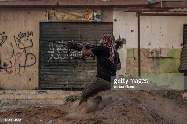 A fighter of Libya's UNbacked Government of National Accord of Fayez Serraj fires his machine gun during clashes with forces of the selfstyled Libyan...