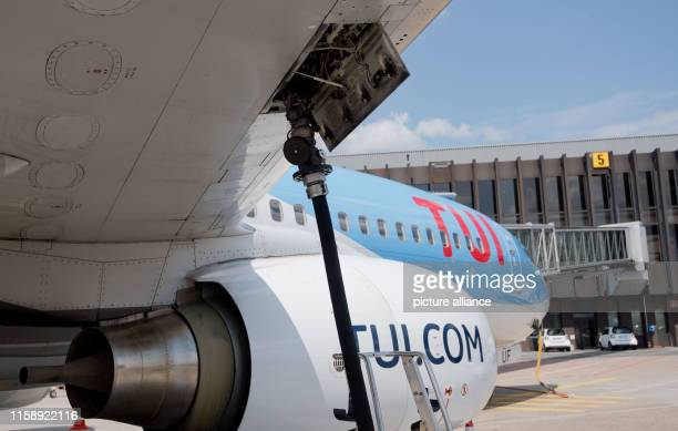 July 2019, Lower Saxony, Hanover: A tanker of AFS Aviation Fuel Services GmbH refuels a Tuifly Boeing 737-800 with kerosene on the apron from Hanover...