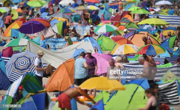 July 2019, Mecklenburg-Western Pomerania, Zinnowitz: Hundreds of people spend the hot summer day crowded together on a Baltic Sea beach on the island...