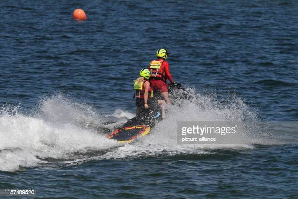 July 2019, Mecklenburg-Western Pomerania, Zinnowitz: Lifeguards of the German Red Cross water rescue service ride a jet ski on the Baltic Sea. Photo:...