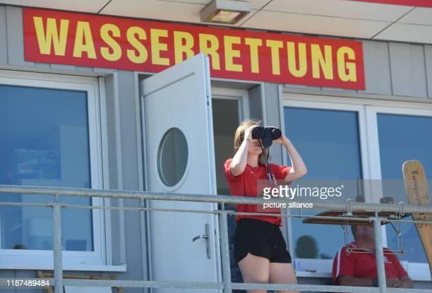 July 2019, Mecklenburg-Western Pomerania, Zinnowitz: Sarah Richter , lifeguard of the German Red Cross , observes from a tower what is happening on...