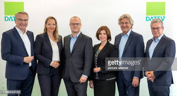 Robert Mayr CEO of the IT service provider Datev eG stands with Eckhard Schwarzer Deputy CEO of Datev and the members of the Datev Executive Board...
