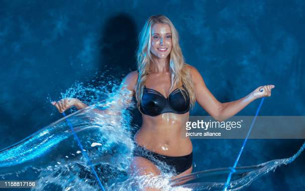 Mareen von Römer volleyball player of the Bundesliga team Dresdner SC gets water poured over her body during the photo shoot for the 22nd DSC...