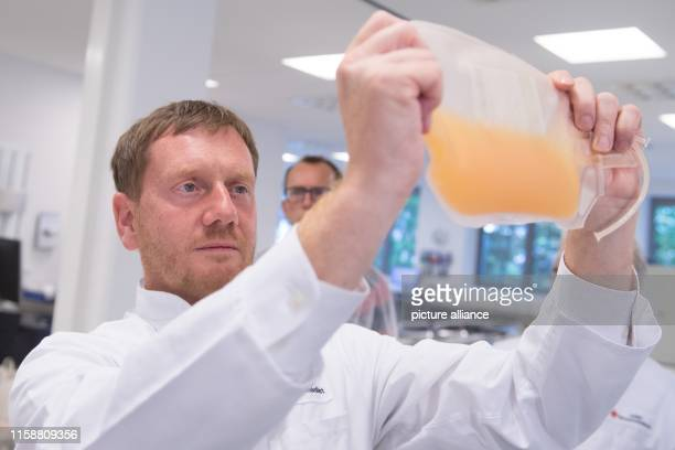 July 2019, Saxony, Dresden: Michael Kretschmer , Prime Minister of Saxony, is holding a bag of blood plasma in the blood preparation unit of the DRK...