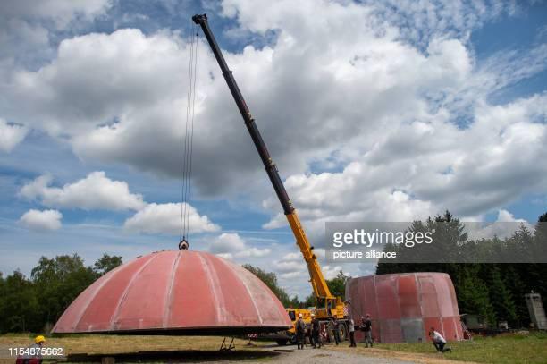 10 July 2019 SaxonyAnhalt Benneckenstein A crane lifts the roof of a former radar dome on the grounds of the Ostdeutsche Fahrzeug und Technikmuseum...