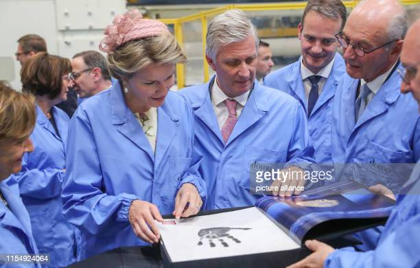 Jan De Clerck owner of the Domo chemical company presents the Belgian royal couple King Philippe and Queen Mathilde with a book in a production line...