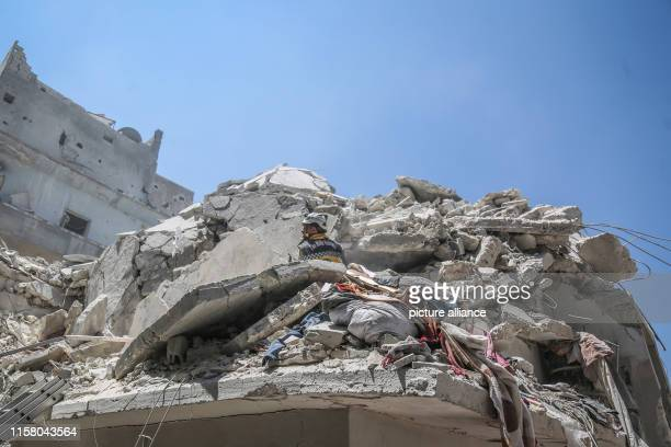A member of the Syrian Civil Defence also known as 'White Helmets' searches for victims or survivors of a reported air strike by proregime forces in...