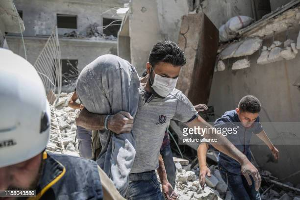 A Syrian man carries the body of a victim of a reported air strike by proregime forces from the rubble of a collapsed building in the town of Ariha...