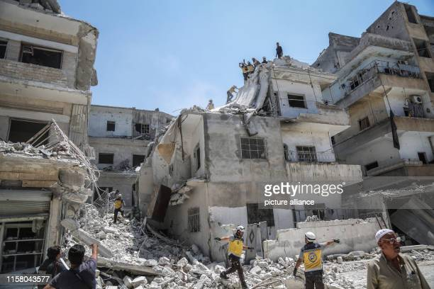 Members of the Syrian Civil Defence also known as 'White Helmets' and Syrian civilians search for victims or survivors of a reported air strike by...