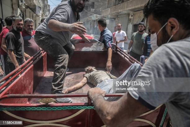 Syrians transport the body of a victim of a reported air strike by proregime forces from the rubble of a collapsed building in the town of Ariha near...