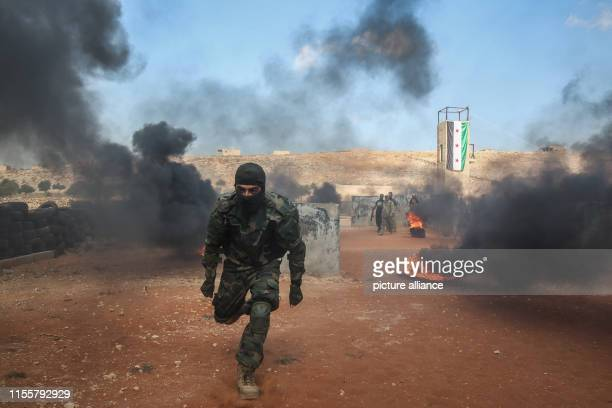 Fighters of Jaysh alIzza formation of the Syrian armed opposition take part in a military show during their graduation from a special forces course...