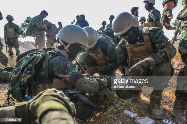 Fighters of Jaysh alIzza formation of the Syrian armed opposition prepare ammunition as they take part in a live fire military exercise as part of a...