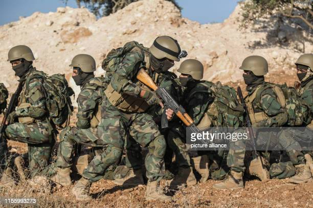 Fighters of Jaysh alIzza formation of the Syrian armed opposition take part in a live fire military exercise as part of a special forces course in...