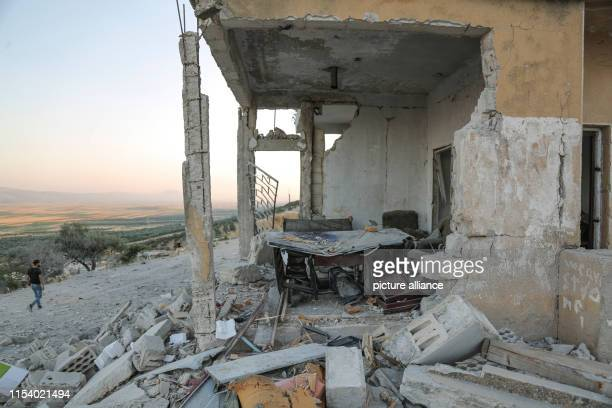 A man walks past a building that was destroyed in an airstrike allegedly carried out the day before by the Syrian government on the town of Muhambal...