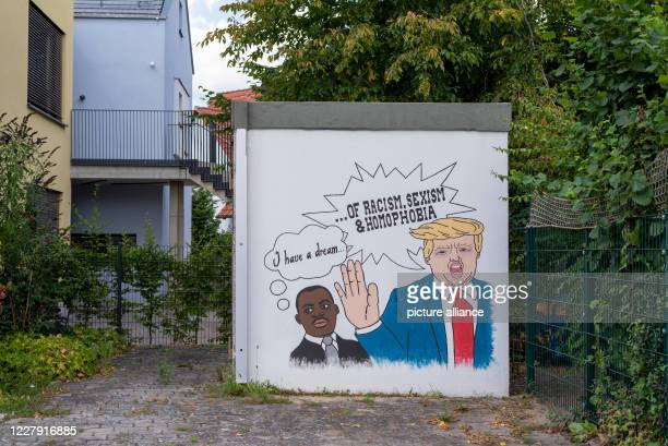 July 2020, Bavaria, Möhrendorf: A comic drawing next to the Protestant Kindergarten shows Martin Luther King and Donald Trump. While King dreams of...