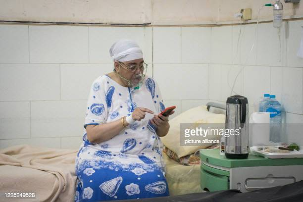 A coronavirus patient breathing through an oxygen mask uses her mobile phone at a ward in the 6th of October Central Hospital which is currently...