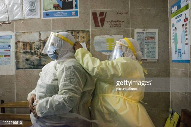 A nurse helps a colleague to put on her personal protective equipment at the 6th of October Central Hospital which is currently serving as an...