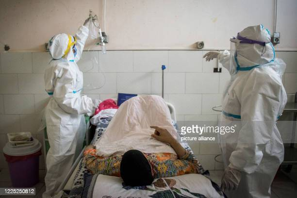Medics wearing personal protective equipment tend to a coronavirus patient at the 6th of October Central Hospital which is currently serving as an...